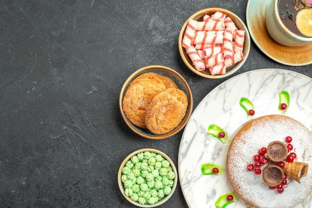 Vista superior em close-up bolo de doces com groselhas doces coloridos waffles biscoitos uma xícara de chá com limão