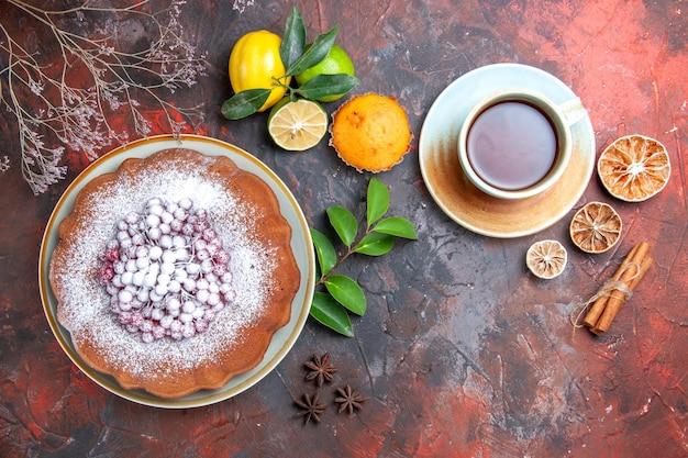 Vista superior em close-up bolo um bolo uma xícara de chá anis estrelado frutas cítricas queque paus de canela
