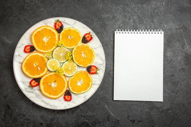 Vista superior em close-up, caderno branco com morangos cobertos de chocolate e prato de fatias de laranja com limão e morangos cobertos com chocolate na mesa escura