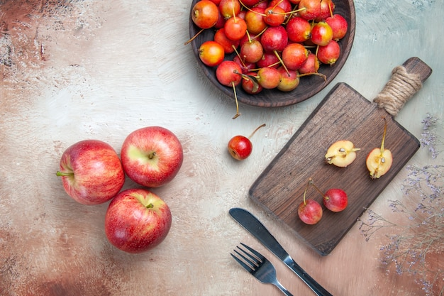 Vista superior em close-up cerejas cerejas na tigela e no quadro faca garfo três maçãs
