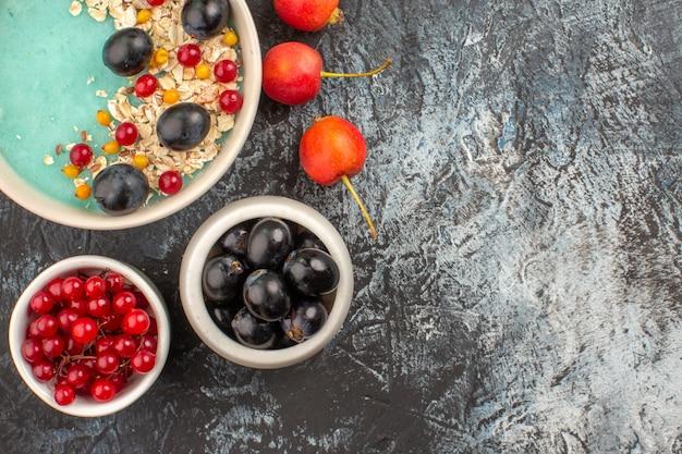 Vista superior em close-up com bagas de groselha e uvas pretas na tigela bagas de aveia no prato cereja
