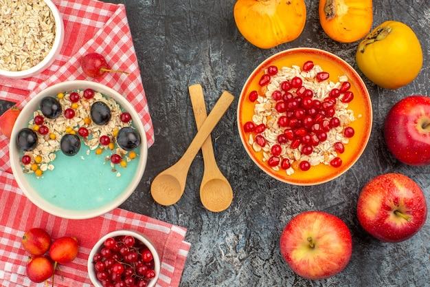 Vista superior em close-up com colheres de frutas e tigelas de caqui e aveia na toalha de mesa