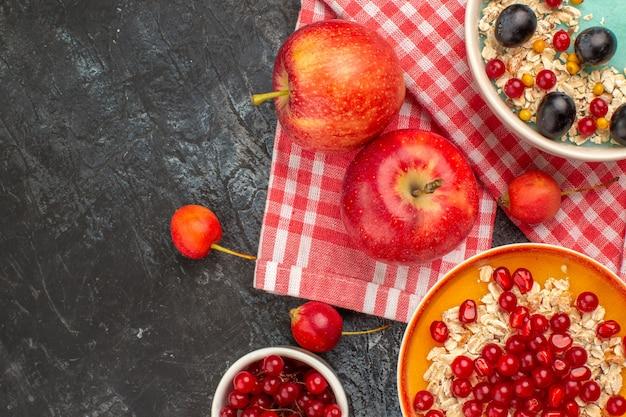 Vista superior em close-up com frutas, duas maçãs, tigelas de groselha, cerejas, uvas, aveia, romã