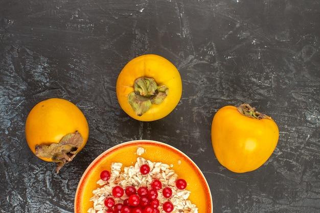 Vista superior em close-up com frutas três caquis as frutas apetitosas na tigela de laranja