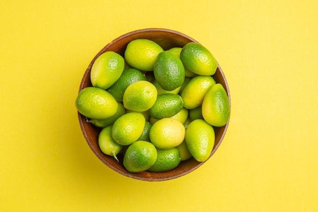Vista superior em close-up com frutas verdes em uma tigela marrom na mesa amarela