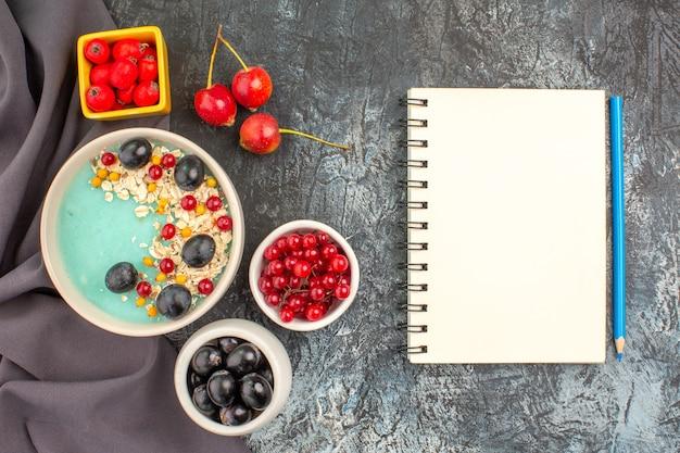 Vista superior em close-up com frutas vermelhas, aveia, frutas coloridas, romã na toalha de mesa, lápis de caderno