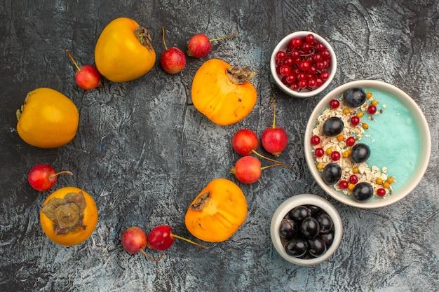 Vista superior em close-up com frutas vermelhas, cereja caqui, ao lado de tigelas de uvas de groselha vermelha