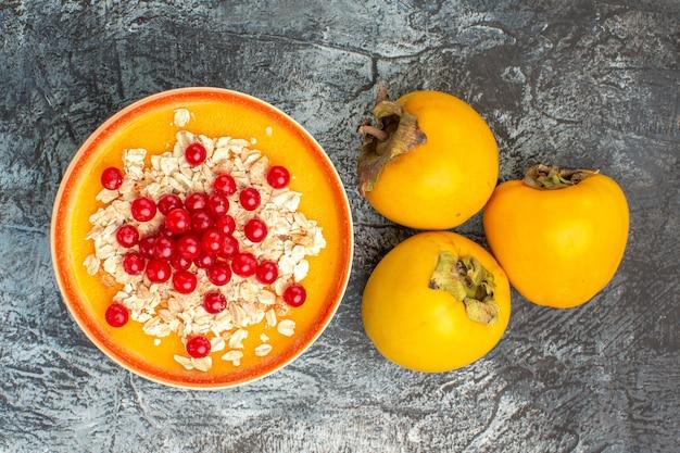 Vista superior em close-up com frutas vermelhas na tigela os apetitosos caquis