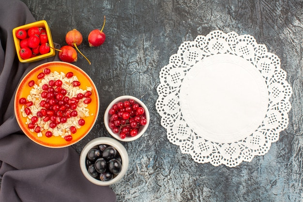 Vista superior em close-up com mingau de aveia e frutas coloridas na toalha de mesa.