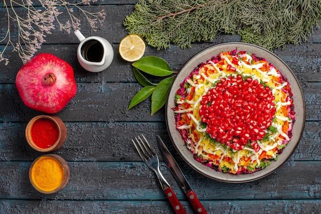 Vista superior em close-up com prato de romãs com romãs ao lado da faca de especiarias com limão de romã e ramos de pinheiro com garfo