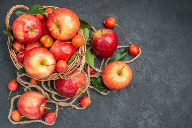 Vista superior em close-up da cesta de frutas com frutas maçãs cerejas com corda de folhas