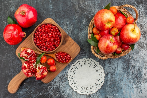 Vista superior em close-up da cesta de frutas com frutas no tabuleiro com colher de romã cerejas rendado guardanapo