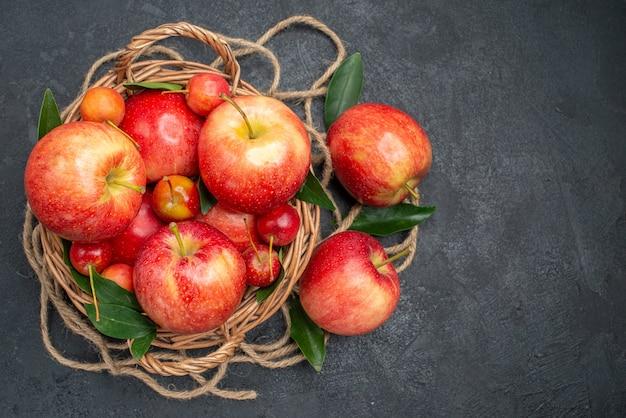 Vista superior em close-up da cesta de frutas das apetitosas maçãs e cerejas com folhas