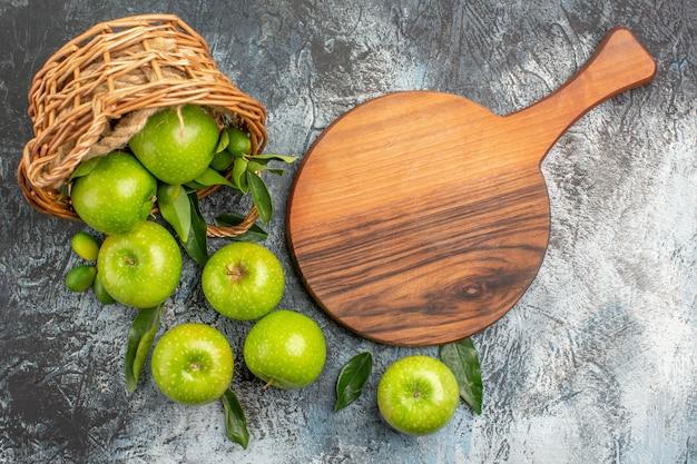 Vista superior em close-up da cesta de maçãs com folhas ao lado da tábua de corte