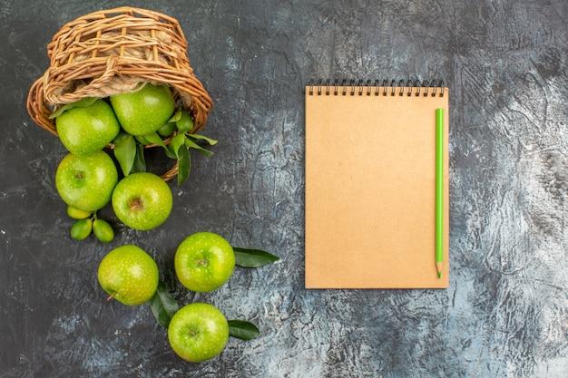 Vista superior em close-up da cesta de maçãs com folhas de lápis de caderno