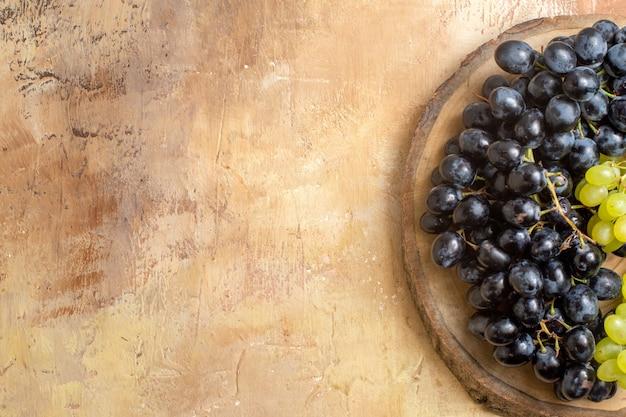 Vista superior em close-up da placa de madeira com uvas verdes e pretas na mesa de creme