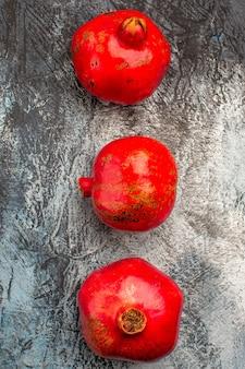 Vista superior em close-up da romã três romãs vermelhas na mesa escura