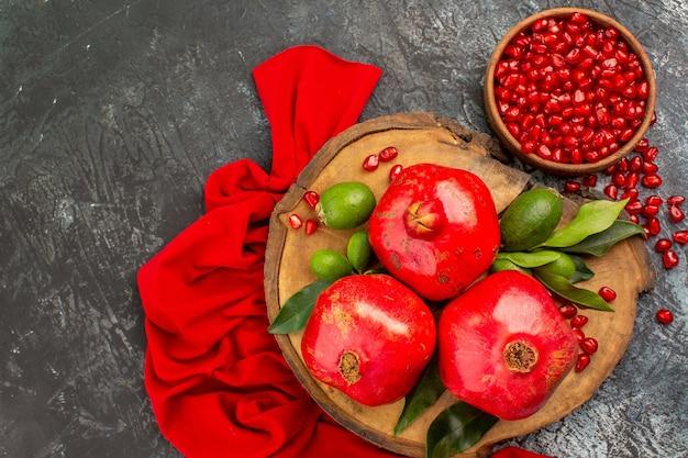 Vista superior em close-up da romã uma tigela de sementes de romã na placa de madeira