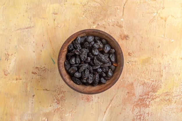 Vista superior em close-up da tigela de uvas com cachos de passas pretas na mesa de creme