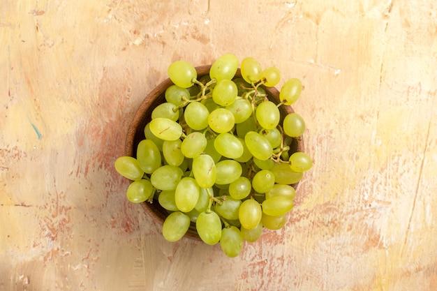 Vista superior em close-up da tigela de uvas com cachos de uvas verdes na mesa de creme