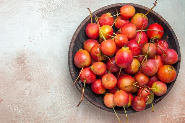 Vista superior em close-up das cerejas as cerejas apetitosas em uma tigela marrom sobre a mesa
