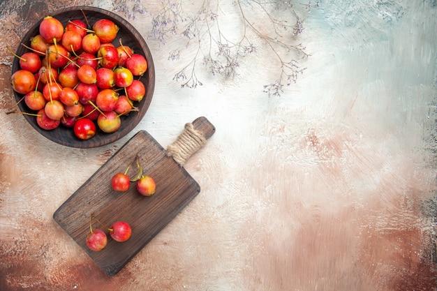 Vista superior em close-up das cerejas na tábua de madeira com galhos de cerejas