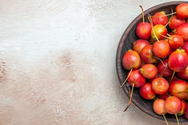 Vista superior em close-up das cerejas tigela marrom das cerejas apetitosas na mesa