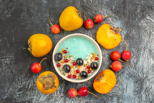 Vista superior em close-up de cereja de frutas vermelhas ao lado de caquis apetitosos em torno da tigela de frutas vermelhas