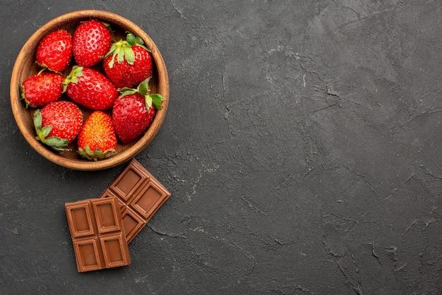 Vista superior em close-up de chocolate e morangos - duas barras de chocolate apetitosas ao lado dos morangos em uma tigela no lado esquerdo da mesa escura