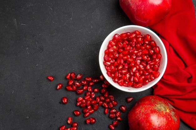 Vista superior em close-up de duas romãs sementes de romã na tigela toalha de mesa vermelha