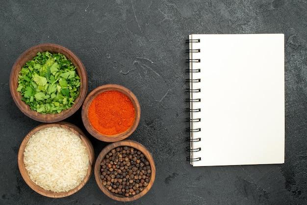 Vista superior em close-up de especiarias e tigelas de caderno de ervas, pimenta preta, arroz e especiarias, ao lado do caderno branco em fundo escuro