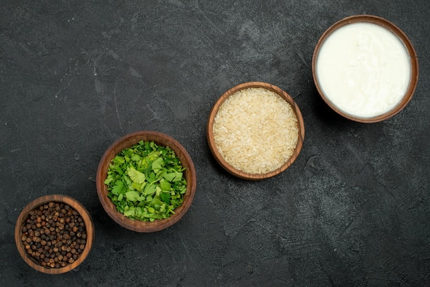 Vista superior em close-up de especiarias em tigelas ervas de papel preto especiarias coloridas arroz no centro da mesa escura