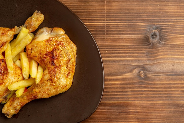 Vista superior em close-up de frango com batata frita em fast food no prato do lado esquerdo da mesa de madeira