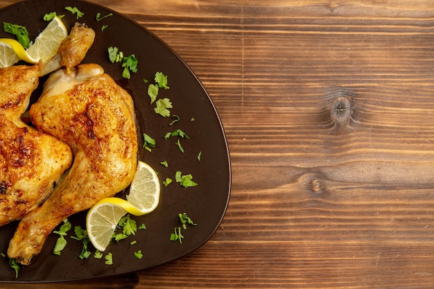 Vista superior em close-up de frango com coxas de frango com limão e ervas e limão no lado esquerdo da mesa