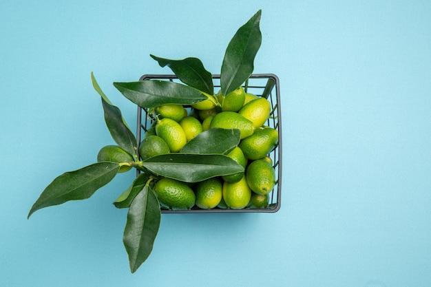 Vista superior em close-up de frutas cítricas cesta cinza de frutas cítricas verdes com folhas
