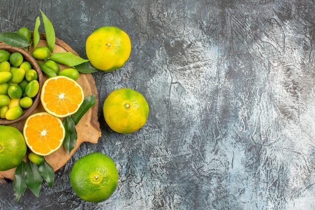 Vista superior em close-up de frutas cítricas diferentes tipos de frutas cítricas na placa de madeira