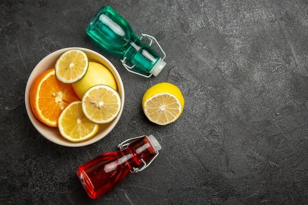 Vista superior em close-up de frutas cítricas frutas cítricas em uma tigela ao lado dos frascos coloridos na mesa escura
