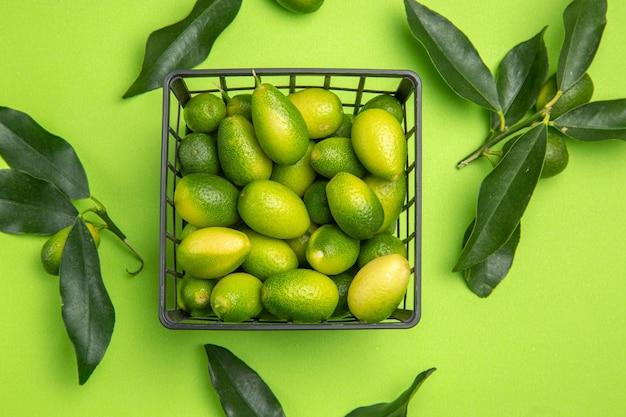 Vista superior em close-up de frutas cítricas na cesta ao lado das folhas verdes na mesa