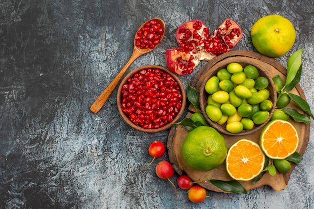 Vista superior em close-up de frutas cítricas tigela de sementes de romã colher frutas cítricas no quadro