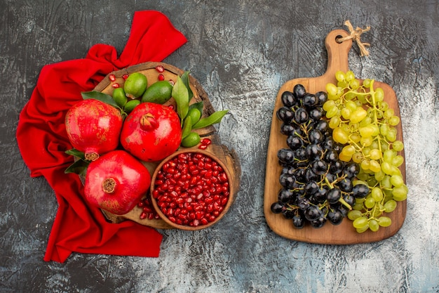 Vista superior em close-up de frutas com romãs na toalha de mesa vermelha e cachos de uvas no tabuleiro