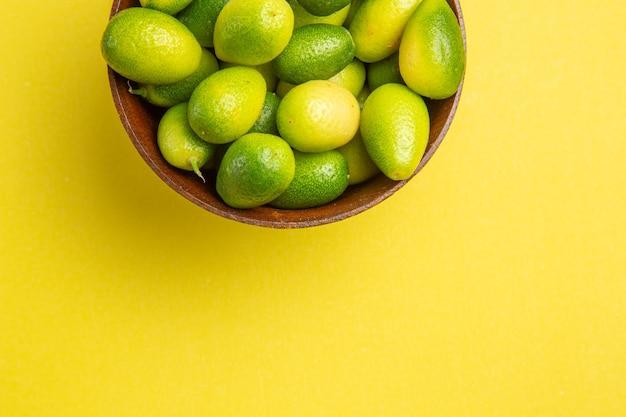 Vista superior em close-up de frutas em uma tigela na mesa amarela frutas verdes na tigela