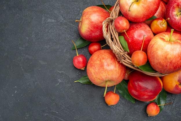 Vista superior em close-up de frutas, frutas vermelhas-amarelas e bagas com folhas na cesta