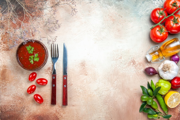Vista superior em close-up de legumes legumes coloridos molho faca garfo na mesa
