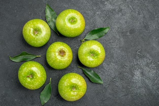 Vista superior em close-up de maçãs com folhas as apetitosas maçãs verdes com folhas na mesa escura