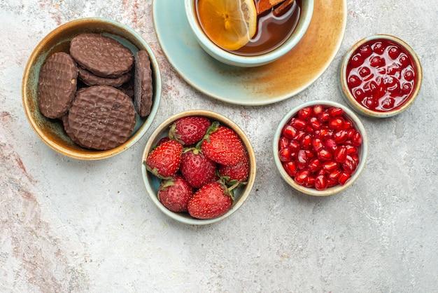 Vista superior em close-up de morangos, uma xícara de chá preto com limão e paus de canela, tigelas de diferentes frutas, biscoitos de chocolate e sementes de romã na mesa