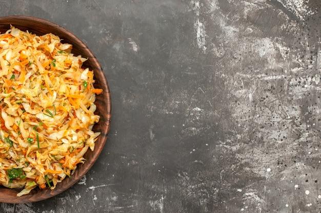 Vista superior em close-up de repolho com cenouras tigela de repolho com cenouras na mesa escura