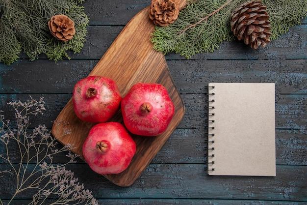 Vista superior em close-up de romãs e romãs vermelhas de caderno na mesa da cozinha ao lado de um caderno branco e galhos de spuce com cones