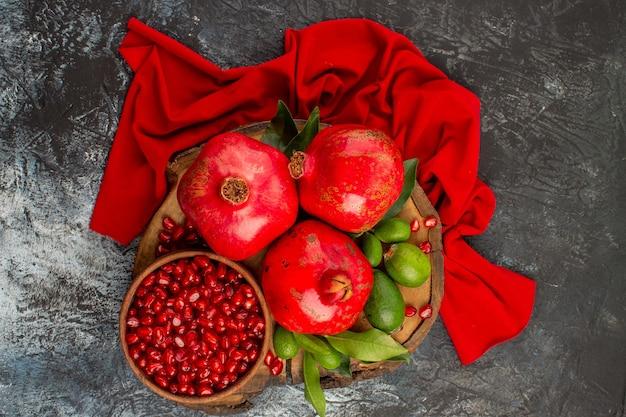 Vista superior em close-up de romãs sementes de romã e romã na toalha de mesa vermelha