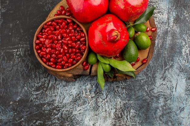 Vista superior em close-up de romãs sementes de romã em uma tigela três romãs na tábua de corte