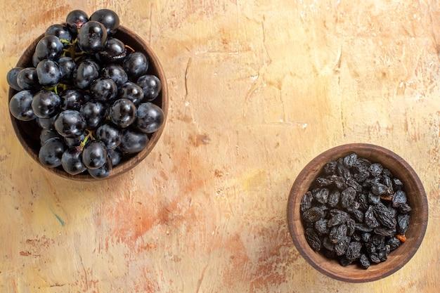 Vista superior em close-up de taças de uvas pretas e passas na mesa